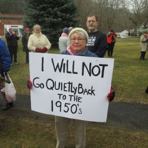 Linda Lloyd of Millerton, N.Y., displays a sign at Saturday's women's protest on the lawn of the White Hart Inn in Salisbury. Ruth Epstein Republican-American