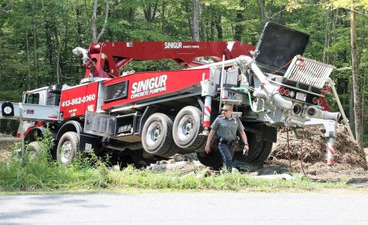 A state trooper walks alongside a Sinigur Concrete Pumping truck that was involved in an accident at a home construction site on Wellsford Court in Goshen on Tuesday. One worker suffered serious injuries and was flown to Hartford Hospital by Life Star helicopter. John McKenna/Republican-American