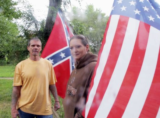 In this August 2017 photo, Bob Jones and Toni Chandler Jones pose for a photo in front of their home in Hebron, N.D., where they have been displaying a Confederate flag. The couple say they donþÄôt intend to take it down following the deadly neo-Nazi rally in Charlottesville, Va. They say the flag stand represents history and part of the American story. (Lauren Donovan/The Bismarck Tribune via AP)