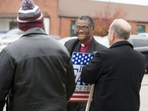 Torrington petitioning mayoral candidate Peter Aduba talks with candidates and supporters holding signs outside the Torrington Armory on Tuesday. Jim Shannon Republican-American