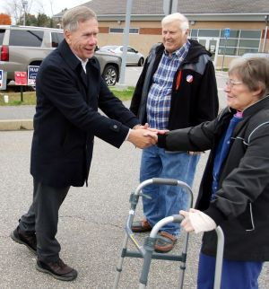 Plymouth Mayor David V. Merchant, a Republican seeking his third term, greets Rodney and Carol Orr of Terryville after voting outside Terryville High School on Tuesday. Steven Valenti Republican-American