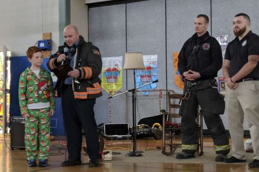 Torrington Fire Lt. Jay Dixon presents Nathan Gryniuk with a plaque to recognize him for providing help and information to assist dispatchers and firefighters when they responded for a medical aid call in October for his mother, Sue. Firefighters and Litchfield County Dispatch surprised Nathan at Torringford School on Friday. Contributed