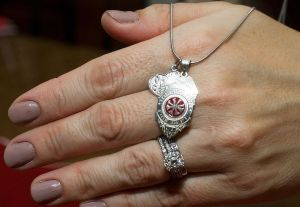 Lori Pepler, wife of late Torrington Deputy Fire Chief Christopher Pepler, shows a necklace someone made depicting the Torrington Fire Department badge at her home on Thursday. Jim Shannon Republican-American