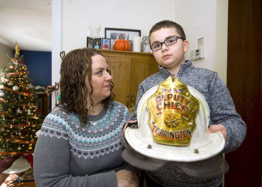 Lori Pepler, wife of late Torrington Deputy Fire Chief Christopher Pepler, looks on as their son, Nathan, 10, holds his father's helmet at their Torrington home on Thursday. Jim Shannon Republican-American