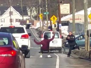 A Waterbury officer with his weapon drawn apprehends a suspect in Thomaston Avenue traffic after a chase. The image, captured by reporter Jonathan Shugarts, was awarded a first place, spot news photo in the New England Newspaper and Press Association.