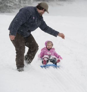 Philip Blosser of Torrington guides his daughter, Emma Grace Blosser, 2, down the snow-covered hill at Major Besse Park in this 2016 photo. Another storm and possibly snow day, are in the forecast for today. Republican-American