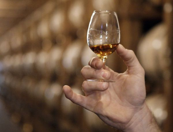 FILE - In this May 20, 2009 file photo, a glass of Jack Daniel's whiskey is examined after being taken from an aging barrel in one of the barrel houses at the distillery in Lynchburg, Tenn. Producers of Kentucky bourbon and Tennessee whiskey scored another round of U.S. sales growth in 2014, while exports topped $1 billion for the second straight year, a distilled spirits trade group said Tuesday, Feb. 3, 2015. (AP Photo/Mark Humphrey, File)