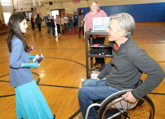 Chris Waddell of Park City, Utah, a paraplegic and one of the most decorated paralympic skiers in U.S. history, brought his message of resilience to Goshen Center School on Wednesday. Waddell chats with fourth-grader Maddie Dorne as school technology specialist Sarah Miller looks on. John McKenna Republican-American