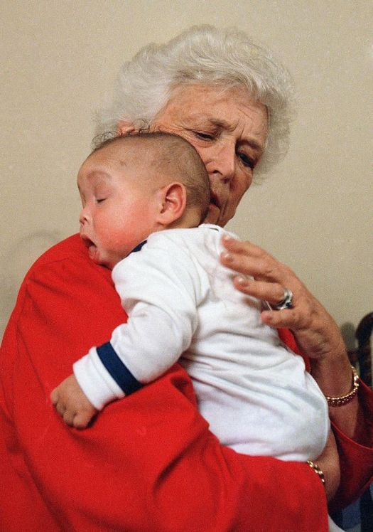 In this March 22, 1989 file photo, first lady Barbara Bush holds an infant identified as Donavan during a visit to Grandma's House in Washington. Grandma's House serves as a house for infants and small children infected with the AIDS virus. Barbara Bush, the snowy-haired first lady whose plainspoken manner and utter lack of pretense made her more popular at times than her husband, President George H.W. Bush, died Tuesday, April 17, 2018. She was 92. (AP Photo/Dennis Cook, File)