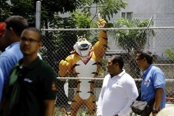 A statue of Kellogg's mascot, Tony the Tiger, stands behind the Kellogg's factory's fence, as workers gather outside in Maracay, Venezuela, Tuesday, May 15, 2018. Workers arriving Tuesday for the early shift were surprised to find a notice taped to an iron gate informing them that the company had been forced to shutter its operations. (AP Photo/Juan Carlos Hernandez)