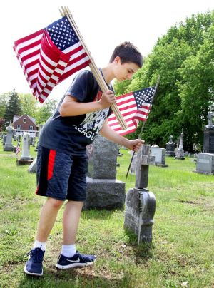 Caleb Goodell, 14, of Winsted, helps his family replace old American flags with new ones Friday at New St. Joseph's Cemetery on Oak Street in Winsted. Steven Valenti Republican-American