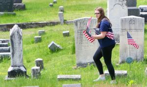 Shelby Goodell, 21, of Winsted, helps her family replace old American flags with new ones Friday at New St. Joseph's Cemetery on Oak Street in Winsted. The family replaces the flags at that cemetery every year before Memorial Day. Steven Valenti Republican-American