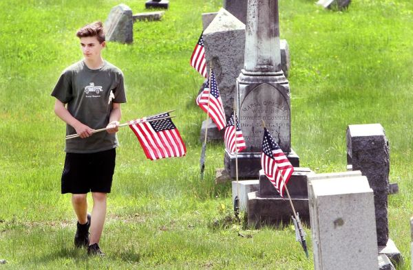 Mason Goodell, 14, of Winsted, helps his family replace old American flags with new ones Friday at New St. Joseph's Cemetery on Oak Street in Winsted. The family replaces the flags at that cemetery every year before Memorial Day. Steven Valenti Republican-American