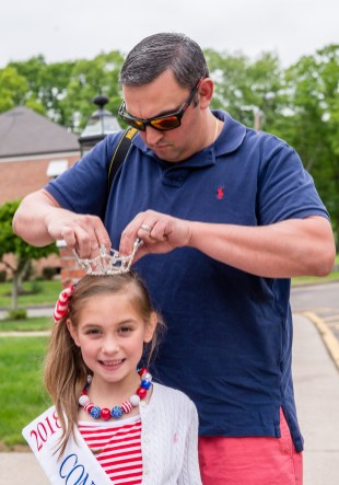 WOLCOTT, CT. 28 May 2018-052818BS352 - Mike Coviello of Prospect helps securing his daughter Julia's, 6, crown before the start of the 2018 Wolcott Memorial Day Parade on Monday evening. Bill Shettle Republican-American