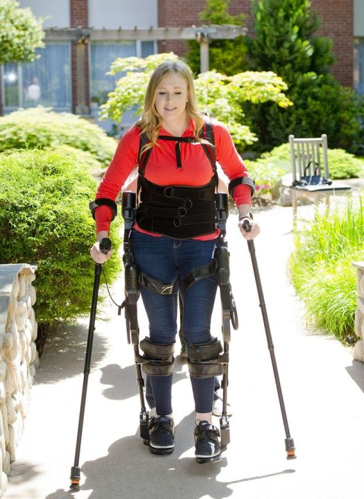 WALLINGFORD, CT-061218JS06-- Jillian Harpin of Wolcott, uses an Ekso robot, a bionic device that enables her to walk, during a therapy session Tuesday at Gaylord Hospital in Wallingford. Harpin, fell from a third floor balcony while on vacation in Mexico in 2016, paralyzing her from the chest down. She is training for the Gaylord Gauntlet, a challenging 5k trail and obstacle run with Thea support team, on Gaylord's campus Jim Shannon Republican American