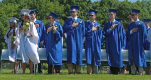 Shepaug Valley School graduates stand for the Pledge of Allegiance during commencement Saturday morning in Washington, Conn. Michael Kabelka / Republican-American