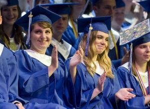 Lewis Mills graduates Savanna Arcuri, left, and Abigail Armington applaud during a speech by Principal Christopher Rau during graduation Thursday at the Warner Theatre in Torrington. Jim Shannon Republican American