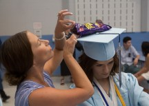Teacher Kristen Collins checked out a bag of snacks on top of Riley Kweder's graduation cap before she graduated from Oxford High School on Wednesday, June 20 in Oxford, Conn. Christopher Burns Republican/American