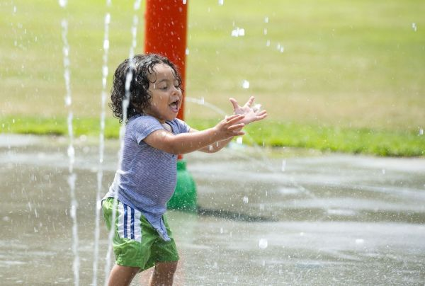 WATERBURY, CT-070318JS03-- 18-month-old Yadiel Jimenez, of Waterbury, keeps cool on Tuesday while playing on the splash pad at Waterville Park in Waterbury with his parents. The heat and humidity is expected to continue through Friday.  Jim Shannon Republican American