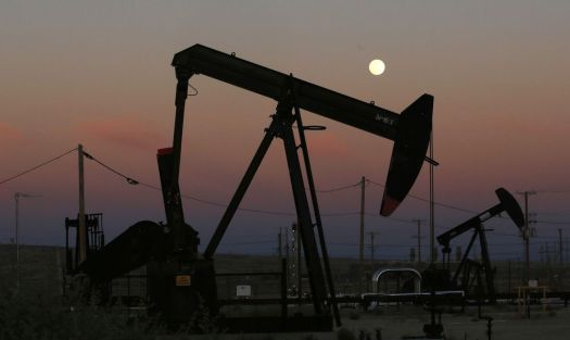 Oil derricks are busy pumping as the moon rises near the La Paloma Generating Station in McKittrick, Calif. The U.S. is on pace to leapfrog both Saudi Arabia and Russia as the world's biggest oil producer.  (Associated Press)