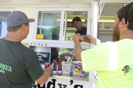 Derek Cisco, owner of Biffdaddy's Roadhouse food truck parked on Railroad Street in Canaan, serves a customer Friday. Ruth Epstein Republican-American