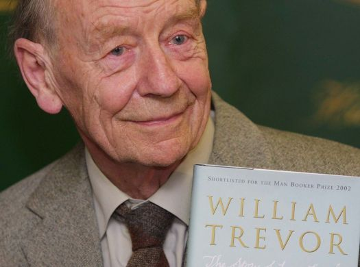 William Trevor holds a copy of his book