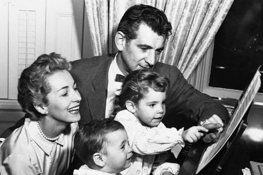 Felicia and Leonard Bernstein with their children, Alexander and Jamie, at home at the piano in 1957.
