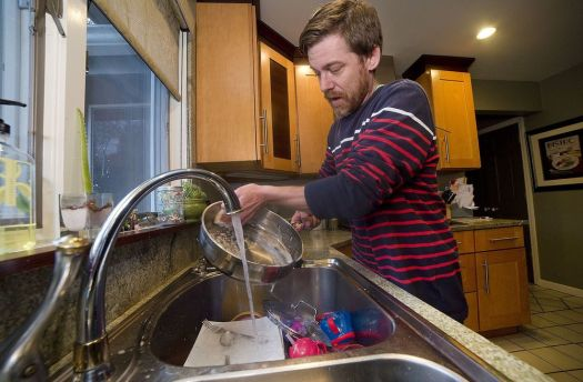 Watertown water and sewer customer Robert Bostrom washes dishes in his Watertown home Friday. Watertown has built up more than $600,000 in delinquent water and sewer payments to the city of Waterbury, refusing to pay higher rates imposed on July 1, 2018. Jim Shannon Republican-American