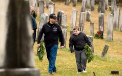 WATERTOWN, CT-121518JS12- Robert Bendler of Naugatuck and his on Chance Bendler, 10, make their way to place wreaths at the graves of veterans during the annual Wreaths Across America ceremony held Saturday at the Old Burying Ground in Watertown. The event was hosted by the Trumbull-Porter Chapter of the Daughters of the American Revolution and the Waterbury Veterans Memorial Committee. Jim Shannon Republican American