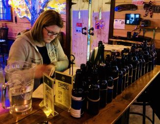 Event organizer Sarah Radawich goes over beer entries at Woodbury Brewing Company's first home brewers competition Sunday in Woodbury.Steve Bigham Republican-American