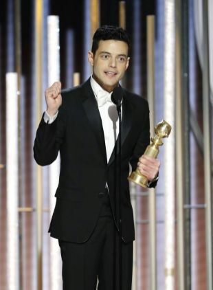 """This image released by NBC shows Rami Malek accepting the award for best actor in a motion picture drama for his role as Freddie Mercury in a scene from """"Bohemian Rhapsody"""" during the 76th Annual Golden Globe Awards at the Beverly Hilton Hotel on Sunday, Jan. 6, 2019, in Beverly Hills, Calif. (Paul Drinkwater/NBC via AP)"""