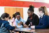 Girls Inc program facilitator Shaniqua Dillard, second from right, plays cards with from left, Ava Montanez 9, Danielle Russell, 7, and Joslyn Tremblay, 10, during playtime in an after school program at the Girls Inc in Waterbury on Friday. Bill Shettle Republican-American