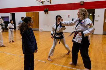 Rita Hubbard a mentor and instructor teaches a small group of girls the martial art of karate, including first degree black-belt Lauren Tuck, 14, center, and red-belt Aviana Thomas, 11, left, looking on during an after school program at the Girls Inc in Waterbury on Thursday. Bill Shettle Republican-American