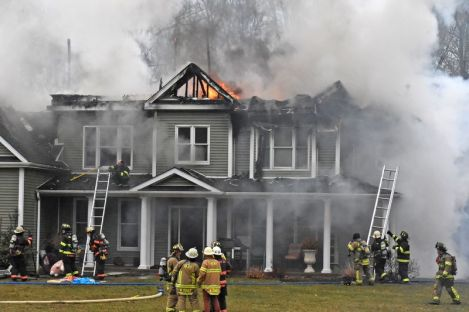 Flames continue to burn through the second floor as firefighters from multiple fire departments attack a fire Sunday afternoon at the home of Marika and Kim Coolbeth at 17 Tamshell Drive in the Kent Hollow section of town. The family was not home at the time the fire began. Lynn Mellis Worthington Republican-American