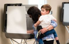 Preston Magill, 2, looks around the Bethlehem Town Hall on Tuesday as his mother Donna Magill casts her ballot during a referendum on the Region 14 school budget Tuesday at Bethlehem Town Hall. Jim Shannon Republican-American