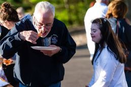 Dr. Peter Jacoby of Saint Mary's Hospital enjoys a hot slice of pizza, with Abbie Senich looking on, during the Greater Waterbury Campership Fund Big Green Truck party at Camp Mataucha in Watertown on Thursday. Bill Shettle Republican-American