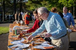 WATR radio personality Tom Chute chooses slices from the many varieties of pizzas from the grand table during the Greater Waterbury Campership Fund's Big Green Truck party at Camp Mataucha in Watertown on Thursday. Bill Shettle Republican-American