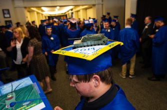 Oliver Wolcott Technical School Mechanical Design and Engineer Technology graduate Derek Jasmin, sports a tank on his cap that he designed and created this year as student gather for graduation ceremonies Wednesday at the Warner Theater in Torrington. Jim Shannon/Republican American