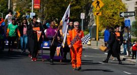 WATERBURY, CT-101919JS02- Race official, Peter Jacoby, leads the bed parade down Grand Street during the third annual United Way of Greater Waterbury's Bed Races held in downtown Waterbury on Saturday. The event is a fundraiser for the United Way. Jim Shannon Republican-American
