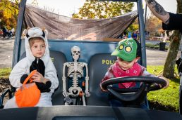 SOUTHBURY, CT. 26 October 2019-102619BS388 - Alessia Hebert, 4, left, looks on with a boney passenger as her brother Cayden, 2, both of Southbury takes her for a spin in the Police ATV vehicle, during the ninth Annual Trick-or-Treat Spooktacular at the Southbury Center Firehouse on Saturday. The firehouse was transformed into a maze of different themed-rooms where kids could collect treats. Bill Shettle Republican-American