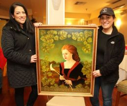 Jennifer Hauck, left, and Melanie Kelly, both of Torrington and volunteers for the Possum Queen Foundation, display a painting that will be auctioned off at the Possum Queen Contest and Auction at the Litchfield Inn on Wednesday. John McKenna Republican-American
