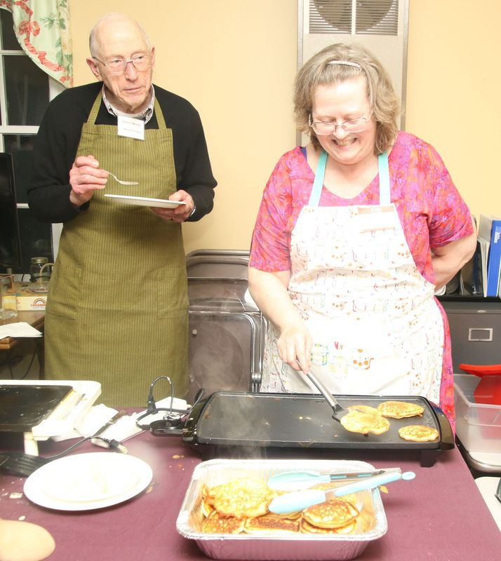 While Malcolm Forbes, senior warden at Trinity Episcopal Church in the Milton section of Litchfield, takes a break, church parishioner Michele Starr cooks pancakes during the church