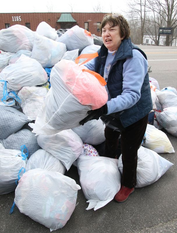 Bobbie Chamalian, founder of Kitty Quarters in Torrington, handles a pile of soft goods and textiles donated to the organization during its annual Clear the Closet drive Saturday. John McKenna Republican-American