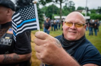 Mike Campbell of Waterbury, a member of the Fat Bastard Motorcycle Club, proudly shows off his Thin Blue Line flag during a rally to support local and national law enforcement Saturday at Seth Thomas Park in Thomaston. Jim Shannon Republican-American