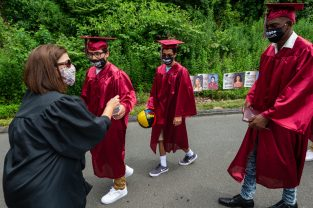 Health and Physical Education teacher Lisa Green hands out bottles of water to graduates as they make their way to graduation ceremonies Friday at Naugatuck High School. The school held five separate ceremonies with about 40 graduates at each due to limitations on gatherings. Jim Shannon Republican-American