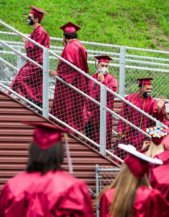 Graduates make their way to the stage to receive their diplomas during graduation ceremonies Friday at Naugatuck High School. The school held five separate ceremonies with about 40 graduates at each due to limitations on gatherings. Jim Shannon Republican-American