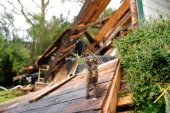 A cat walks through debris at Chris Johnson's home on Thursday, Aug. 27, 2020, in Lake Charles, La., after Hurricane Laura moved through the state. Johnson stayed in his home as the storm passed. (AP Photo/Gerald Herbert)