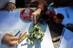 The hands of a participant holding a branch of dry Spearmint on top of a wooden table; on the same wooden table, are also two clay cups, two small red plates, crayons of different colors (yellow, blue, red, purple), two small glass jars, white pieces of paper with notes, and a couple of flyers with information about La morada restaurant. Photo by Cinthya Santos-Briones for Brewing Memories workshop, October 3, 2020.