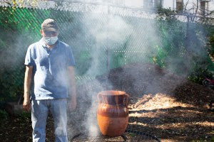 Antonio, who is wearing a light blue shirt, jeans, a baseball cap, and medical mask, stands near a fire. There's a big pot made out of clay on top of the fire; smoke comes out of the fire. The mounds of soil in the background reflect the morning sunlight.