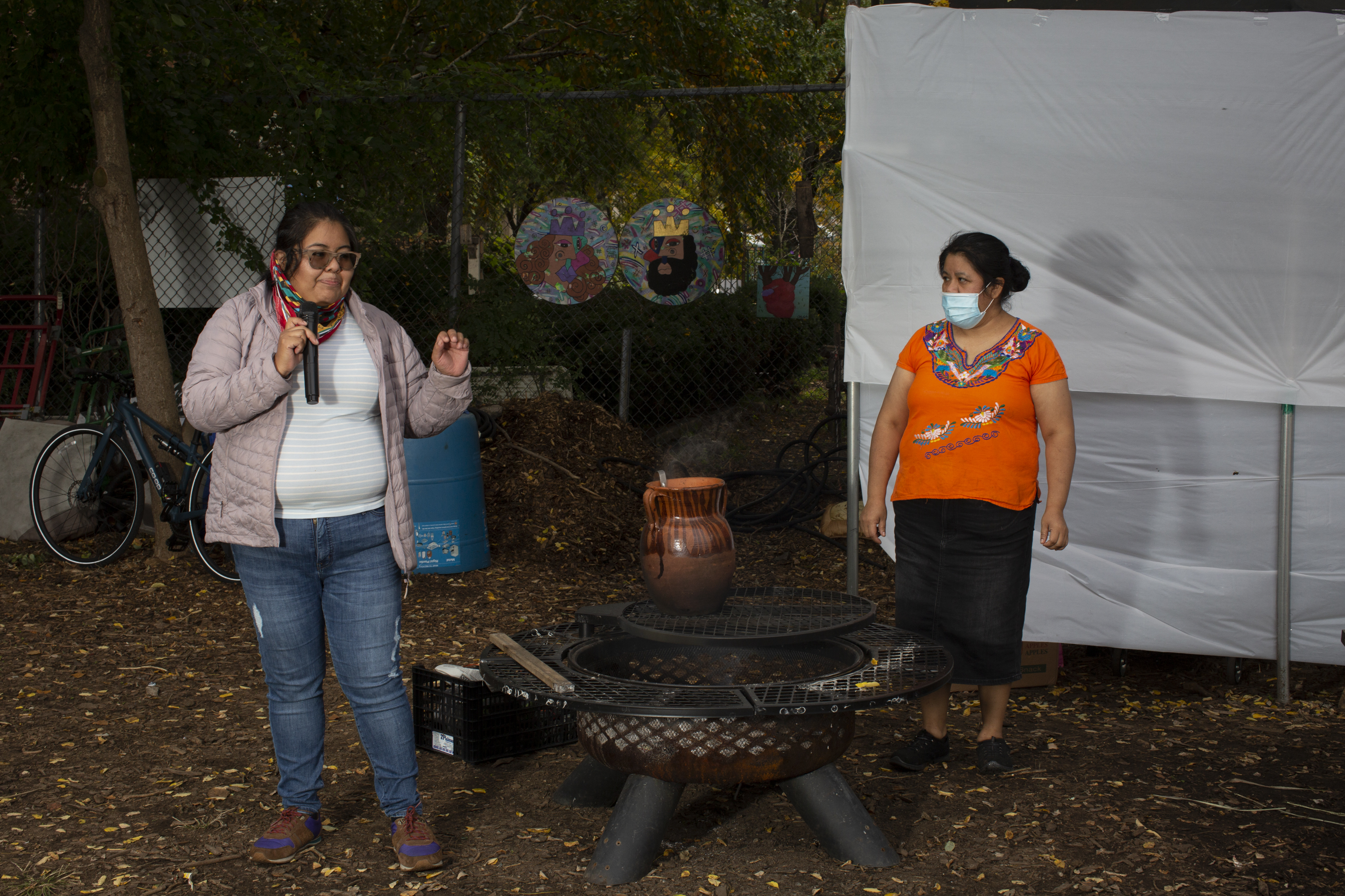 Yajaira, wearing a white shirt, a soft pink jacket, a scarf, and jeans, shares a memory with the participants of the workshop (out of frame). She stands near the fire. Natalia stands near Yajaira, to her left, wearing an Indigenous Mexican embroidered shirt (orange with flowers), a long black skirt, and a medical mask. Photo by Cinthya Santos-Briones for Brewing Memories workshop, October 24, 2020.
